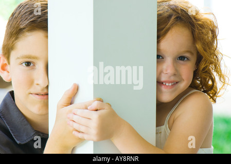 Brother and sister peeking around column at camera, holding hands, smiling - Stock Photo