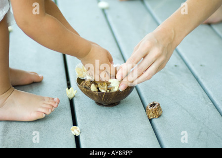 Mother and daughter picking up potpourri from bowl, cropped view - Stock Photo