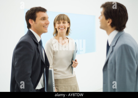 Three business associates standing together, having a discussion, smiling - Stock Photo