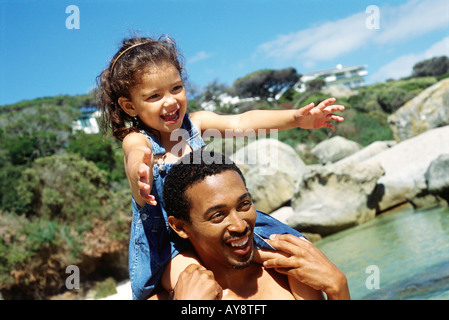 Father carrying daughter on shoulders at the beach, both smiling, close-up - Stock Photo