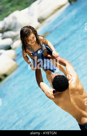 Father lifting daughter in the air at the beach, rear view - Stock Photo