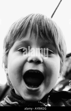 Little boy looking at camera, mouth open wide, portrait - Stock Photo
