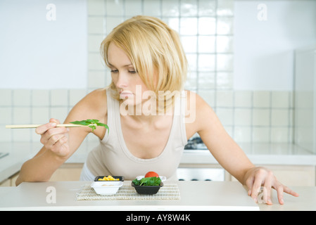 Young woman leaning over kitchen counter, picking up herbs with chopsticks - Stock Photo