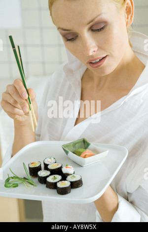 Woman holding maki sushi and chopsticks, looking down - Stock Photo