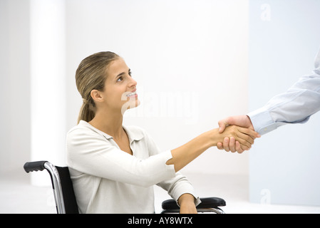 Woman in wheelchair shaking hands with businessman, cropped - Stock Photo