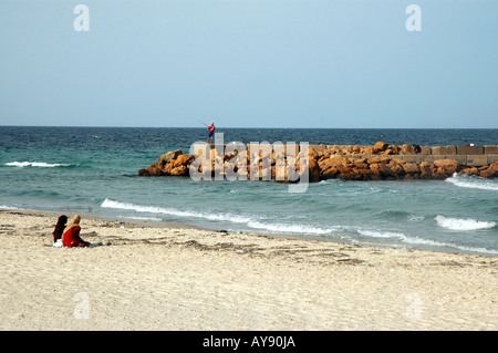 Two tunisian woman sitting on a beach in Sousse city in Tunisia - Stock Photo