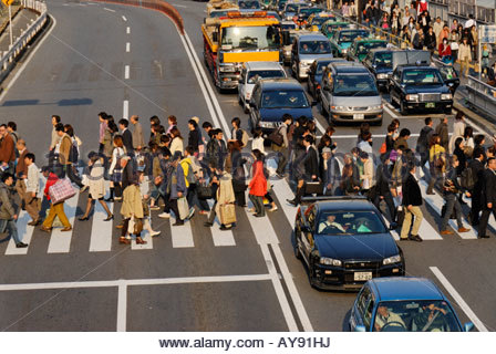 people walking across a 'zebra crossing' on Koshu-Kaido Avenue in front of Shinjuku station - Stock Photo