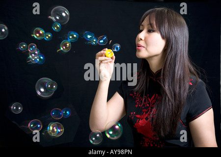 Chinese girl blowing bubbles - Stock Photo