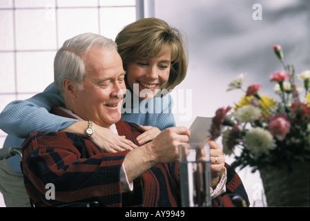 Daughter reading get well card to Recuperating wheelchair bound father in hospital - Stock Photo