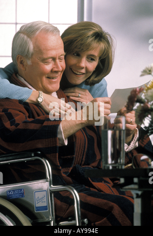 Daughter reading get well card toher  Wheelchair bound father in hospital - Stock Photo