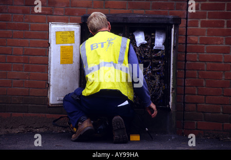 British Telecom engineer working on a telephone junction box in the village of Alderton, Suffolk, UK. - Stock Photo