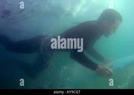 Joss Ash underwater duck diving, Chapel Porth, Cornwall, UK - Stock Photo