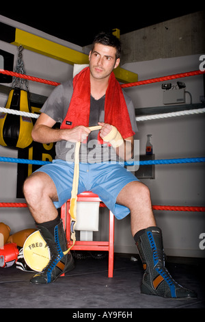 Boxer taping hands in boxing ring - Stock Photo