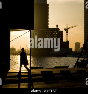Walking man during sunset Behind him the Rijnhaven on the south of the Wilhelmina pier - Stock Photo