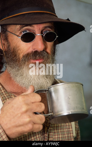 MR 0364 Old wrangler Leonard Clapes drinks cowboy coffee from a battered tin cup in Lincoln, New Mexico. - Stock Photo