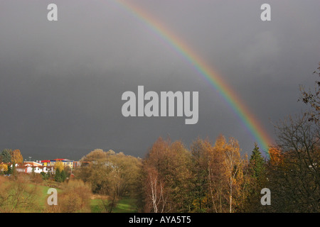 Rainbow at the edge of a village above trees in autumn folige - Stock Photo