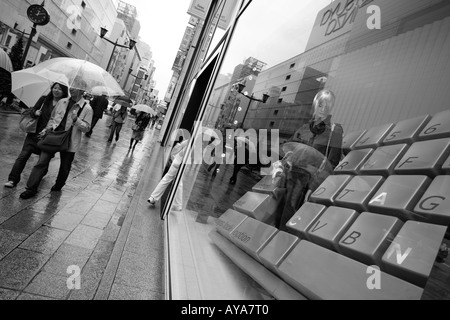 Asia Tokyo Japan Shoppers carrying umbrellas walking past department store window on rainy afternoon in Ginza District - Stock Photo