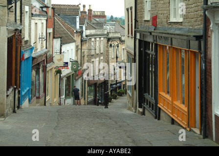 Frome one of a number of quaint narrow hilly side streets which house a selection of small shops and eating venues - Stock Photo