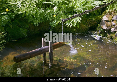 Water spilling from Bamboo boar scarer in pond at Japanese garden in Butchart Gardens Victoria British Columbia - Stock Photo