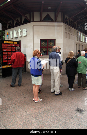 Queue of people waiting to purchase theatre tickets from booking kiosk - Stock Photo