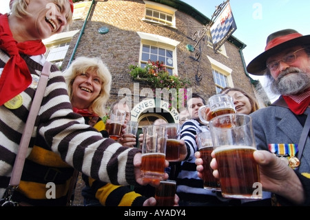 A crowd of regulars at a traditional Sussex pub raise a glass of their favourite brew. - Stock Photo