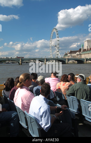 London River Thames passengers on tour boat with Westminster Bridge and British Airways Millennium eye Ferris wheel - Stock Photo