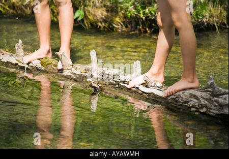 Children standing on a log in a stream - Stock Photo