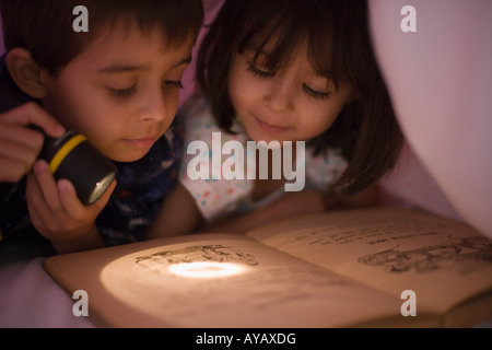 Reading under the covers by torchlight girl aged four years boy aged six - Stock Photo