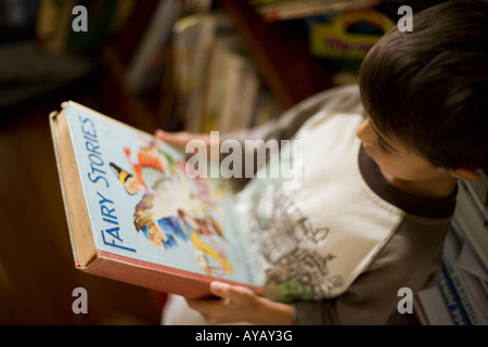Boy aged six years reads book of Fairy Tales and Nursery Rhymes. - Stock Photo