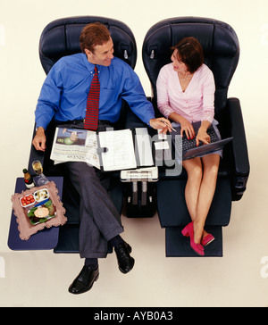 Business Executives travelling with using Laptop Computer sitting in First Class - Stock Photo