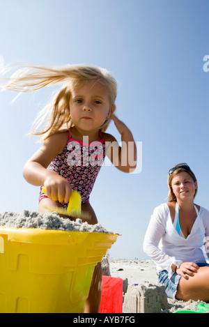Mother and daughter building sandcastles on the beach - Stock Photo