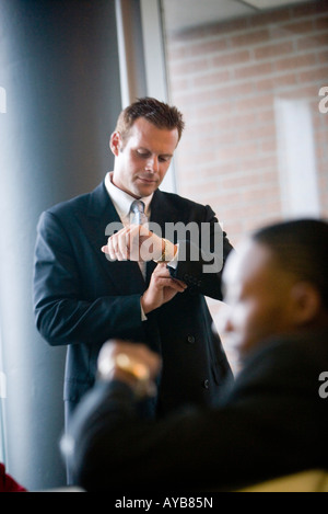 Business people sitting and waiting in an office lobby, looking at their watches - Stock Photo