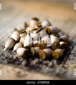 A collection of poppy seed heads with seeds scattered on a wooden bench. - Stock Photo