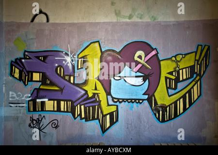 A piece of graffiti in a brownfield site factory. Graffiti dans une usine désaffectée. - Stock Photo