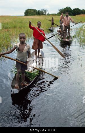 Children of Libinza tribe going to school by canoe Ngiri river region Democratic Republic of the Congo ex Zaire - Stock Photo