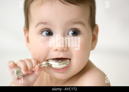 6 month old caucasian baby girl with silver rattle in her mouth - Stock Photo