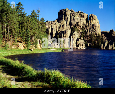 Sylvan Lake in Custer State Park in South Dakota is bounded by forested hills and dramatic granite rock monoliths - Stock Photo