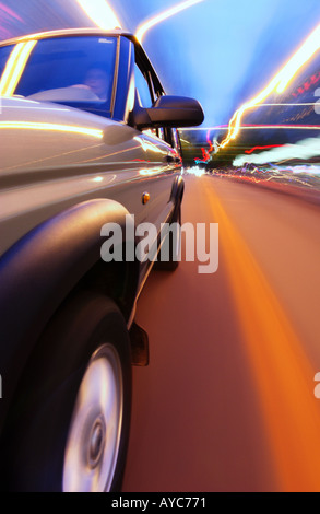 Side view of suv driving at night with street and lights blurring in background - Stock Photo