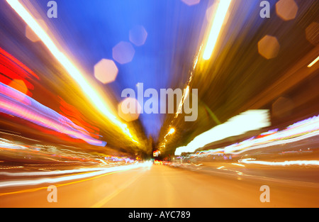 View from front bumper of a car with lights and street streaking by - Stock Photo