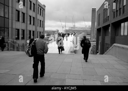 Pedestrians cross the Millenium Bridge, London, UK, England - Stock Photo