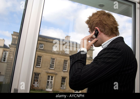 businessman talking on a mobile phone looking out of the window geogian house - Stock Photo