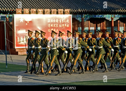 Soldiers practising military marching under a propaganda billboard, near Beijing's Forbidden City and Tiananmen - Stock Photo