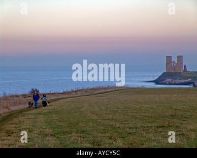 hiking along the cliff tops at sunset norman church in background , reculver england - Stock Photo