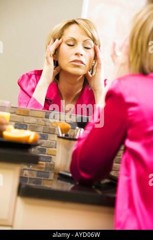 Woman massaging her head in mirror - Stock Photo
