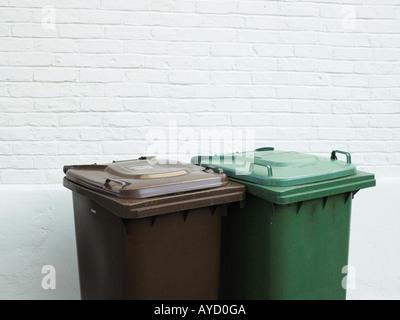 Rubbish bins against white brick wall - Stock Photo
