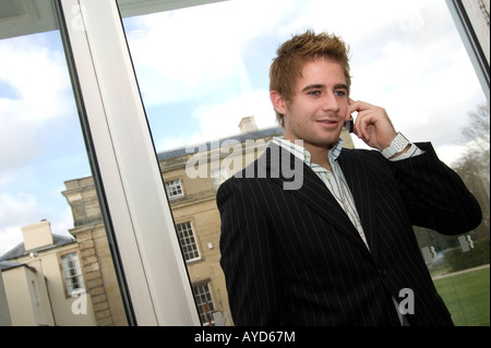 young businessman talking on a mobile phone by a window - Stock Photo