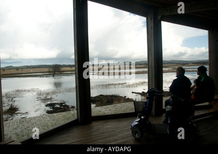 three people in hide at Cors Caron RSPB Royal Society for the Protection of Birds nature reserve Tregaron Ceredigion - Stock Photo