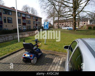 Scootmobile parked in a handicapped spot Vught Noord Brabant the Netherlands - Stock Photo