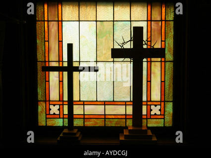 Two religious crosses sitting in a stained glass window sill of a church - Stock Photo