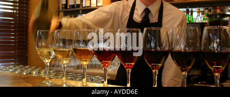 Contemporary bar shot of barman pouring wine into glasses for a tasting - Stock Photo